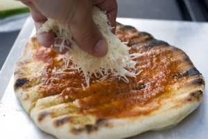 Sprinkle Cheese onto Grilled Pizza
