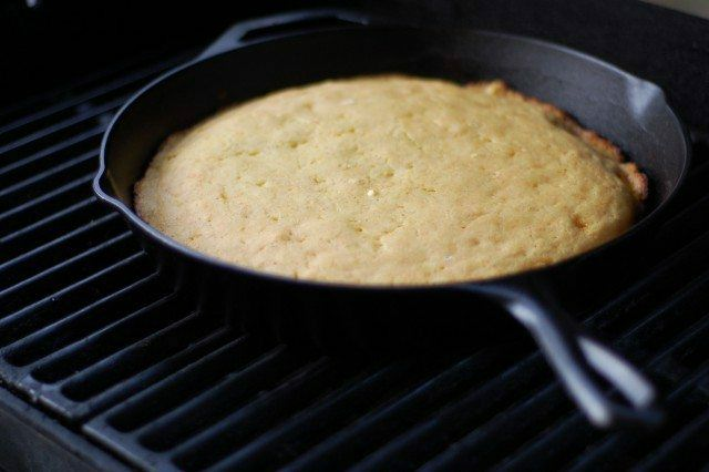 Golden brown cornbread in a cast iron skillet on the grill