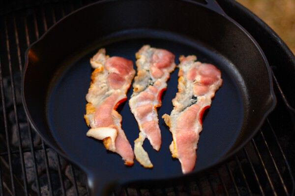 Bacon cooking on the grill in a cast iron skillet