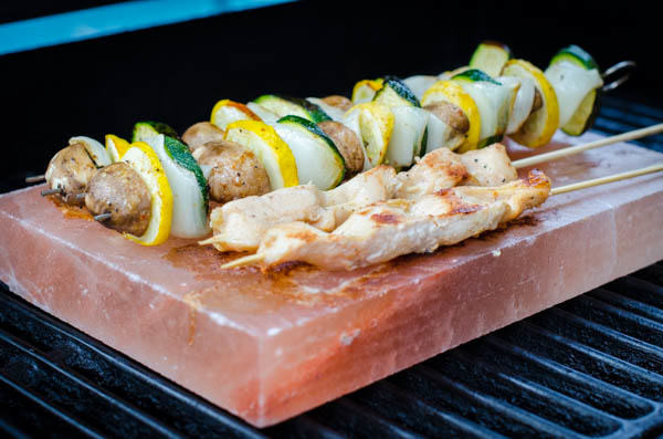 chicken and veggies on a salt block